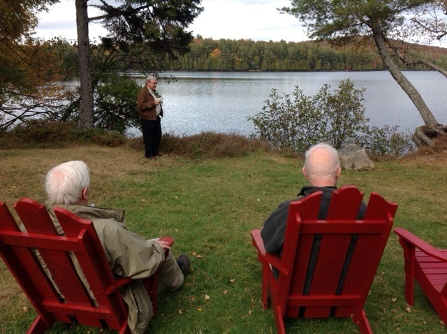 2 men in red chairs looking over sagamore and one man standing near lake