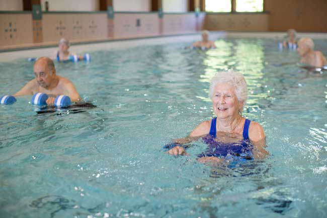 woman in blue suit in a pool aerobics class