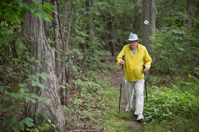 woman in yellow jacket walking on a trail