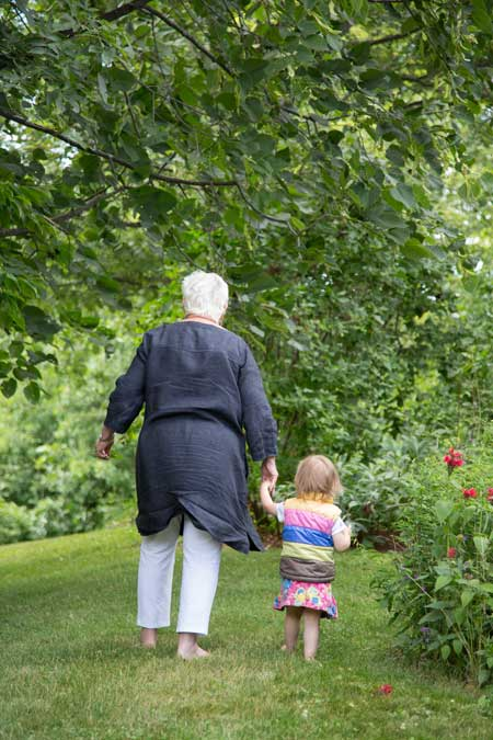 white haired woman walking , holding the hand of a toddler